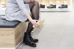 Femme essayant sur de nouvelles chaussures dans le magasin de chaussures Achetez les nouvelles chaussures dans la boutique du cen Photos stock