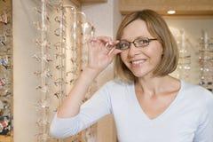 Femme essayant sur des lunettes aux optométristes image stock