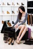 Femme essayant sur des pompes dans la boutique Photos libres de droits