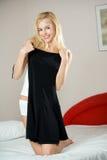 Femme essayant sur la robe à la maison photographie stock