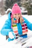 Femme essuyant le pare-brise de véhicule utilisant la neige de balai Photographie stock