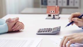 Femme et agent immobilier comptant sur la calculatrice banque de vidéos