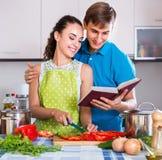 Femme et ami de sourire avec le livre de cuisine Photo stock