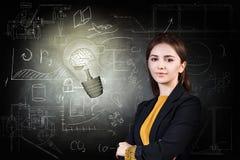 Femme et ampoule lumineuse au-dessus de fond d'icônes Image stock