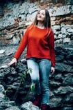 Femme et avant rouge de poziruye de robes longues de l'appareil-photo sur le fond Image stock