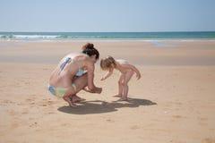 Femme et bébé rassemblant des coquilles de mer Image libre de droits