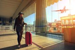 Femme et bagage de déplacement marchant en terminal et air d'aéroport Image libre de droits
