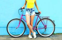 Femme et bicyclette de mode d'été sur un bleu coloré Photo libre de droits