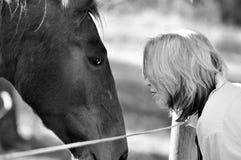 Femme et cheval affectueux mous blancs noirs de tendresse Images libres de droits