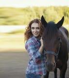 Femme et cheval ensemble près de la stalle Photographie stock libre de droits