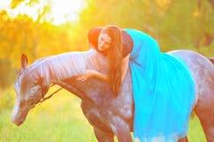 Femme et cheval gris dans la lumière d'or Photographie stock libre de droits