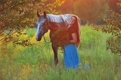 Femme et cheval gris dans la lumière d'or Photographie stock