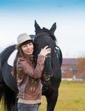 Femme et cheval, pull beige, veste en cuir, jeans, chapeau, Cl Photo stock