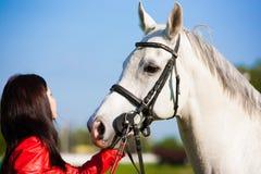 Femme et cheval Veste en cuir haute de portrait et rouge étroite Photo stock