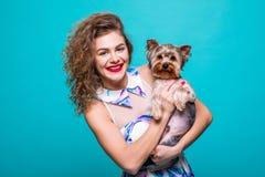 Femme et chien dans une robe Femme heureuse avec un chien - d'isolement au-dessus d'un fond vert Beau jeune femme retenant le pet photo stock