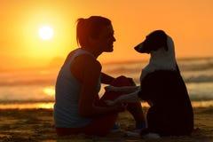 Femme et chien ensemble au coucher du soleil Photos stock