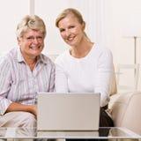 Femme et descendant aînés à l'aide de l'ordinateur portatif Photographie stock