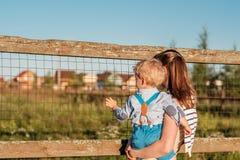 Femme et enfant à la ferme regardant l'autruche Photographie stock