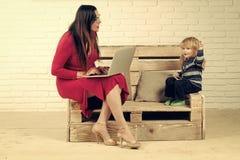 Femme et enfant avec l'ordinateur portable, éducation incluse Photographie stock libre de droits