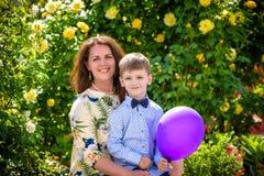 Femme et enfant avec le baloon sur le fond vert Concept de vacances de famille de ressort Fête des mères Photo stock