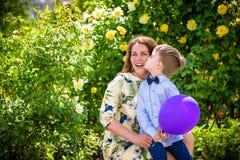 Femme et enfant avec le baloon sur le fond vert Concept de vacances de famille de ressort Fête des mères Photo libre de droits