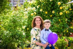 Femme et enfant avec le baloon sur le fond vert Concept de vacances de famille de ressort Fête des mères Photographie stock