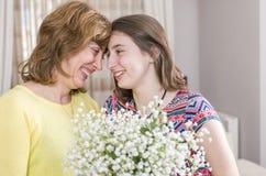 Femme et enfant avec un bouquet des fleurs dans leur maison Jour du `s de mère Photos stock