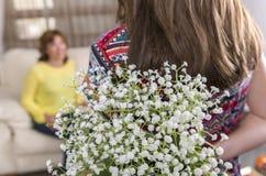 Femme et enfant avec un bouquet des fleurs dans leur maison Jour du `s de mère Images stock