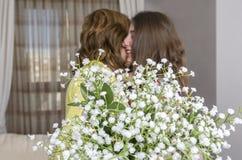 Femme et enfant avec un bouquet des fleurs dans leur maison Jour du `s de mère Photographie stock