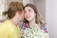 Femme et enfant avec un bouquet des fleurs dans leur maison Jour du `s de mère Photo libre de droits