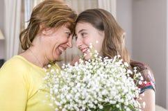 Femme et enfant avec un bouquet des fleurs dans leur maison Jour du `s de mère Photographie stock libre de droits