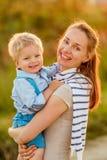 Femme et enfant ayant l'amusement dehors dans la lumière du soleil de coucher du soleil Photographie stock libre de droits
