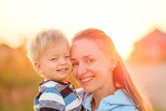 Femme et enfant ayant l'amusement dehors dans la lumière du soleil de coucher du soleil Photo stock