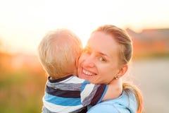 Femme et enfant ayant l'amusement dehors dans la lumière du soleil de coucher du soleil Image stock