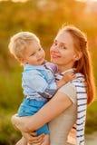 Femme et enfant ayant l'amusement dehors dans la lumière du soleil de coucher du soleil Image libre de droits