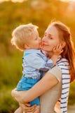 Femme et enfant ayant l'amusement dehors dans la lumière du soleil de coucher du soleil Photos libres de droits