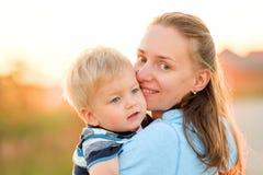 Femme et enfant ayant l'amusement dehors dans la lumière du soleil de coucher du soleil Images libres de droits