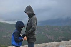 Femme et enfant dans des vestes avec des capots dans le Caucas Photos libres de droits