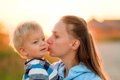 Femme et enfant dehors au coucher du soleil Enfantez embrasser son fils Photographie stock