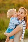 Femme et enfant dehors au coucher du soleil Garçon embrassant sa maman Image libre de droits