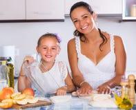 Femme et enfant faisant cuire le strudel Photo stock