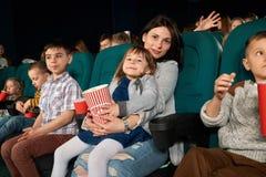 Femme et enfant s'asseyant dans le théâtre de film et posant à l'appareil-photo Photos stock