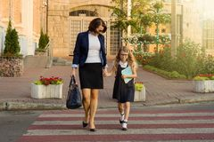 Femme et enfant - une jeune écolière tenant des mains, sur le Cr de zèbre Photographie stock libre de droits