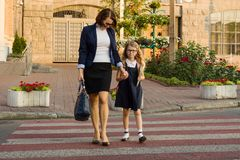 Femme et enfant - une jeune écolière tenant des mains, sur le Cr de zèbre Images stock