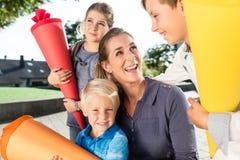Femme et enfants au jour d'inscription avec des cônes d'école Images stock