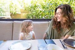 Femme et fille dans le restaurant riant avec l'expression drôle Photos stock