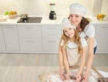 Femme et fille dans les tabliers et des chapeaux de chef faisant la forme de coeur images stock