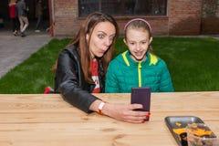 Femme et fille prenant Selfie avec le téléphone portable Photos stock