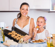 Femme et fille tenant le plateau de cuisson Images stock