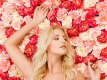 Femme et fond complètement des roses photographie stock